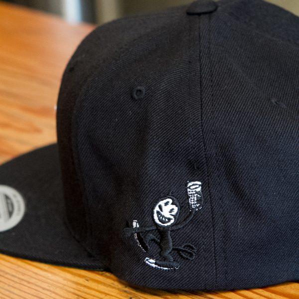 Close up of devil cat embroidered Fall Brewing Company hat in black